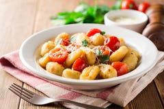Gnocchi italien fait maison avec la tomate, l'ail, le persil et le parmesan sur la table en bois Photos stock