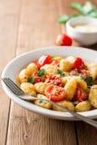 Gnocchi italien fait maison avec la tomate, l'ail, le persil et le parmesan sur la table en bois Photo libre de droits