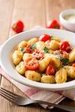 Gnocchi italien fait maison avec la tomate, l'ail, le persil et le parmesan sur la table en bois Photos libres de droits