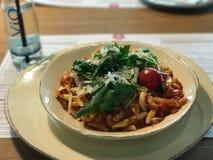 Gnocchi met tomatensaus, parmezaanse kaaskaas, kersentomaat en peterselie stock foto