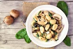 Gnocchi with mushroom sauce, spinach & chicken, above scene on wood. Gnocchi with a mushroom cream sauce, spinach, chicken and sun dried tomatoes, above scene on Stock Photo