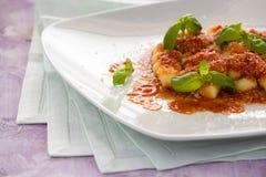 Gnocchi, pastas italianas con albahaca de la salsa de tomate y chee del parmesano Foto de archivo libre de regalías