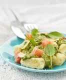 Gnocchi with pesto sauce and smoked salmon Stock Photos