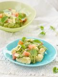 Gnocchi with pesto sauce and smoked salmon Stock Photography