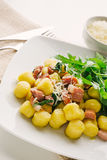 Gnocchi. Potato dumplings with bacon and arugula leaves Stock Image