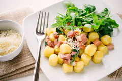 Gnocchi. Potato dumplings with bacon and arugula leaves Stock Photos