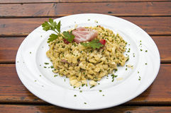 Gnocchi of potatoes with ham,parmesan and herbs. Typical dish of italian alps Royalty Free Stock Photos