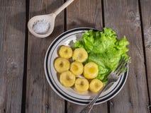 Gnocchi pré-feito da batata com as folhas da alface de folha fresca em uma placa cerâmica com listras, uma forquilha da tabela e  foto de stock royalty free
