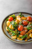 Gnocchi with spinach, garlic and tomatoes Stock Photos
