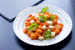Gnocchi in tomato sauce with green fresh basil and mozzarella balls served on a plate. Cooked italian gnocchi from potatoes in tomato sauce with green fresh royalty free stock image