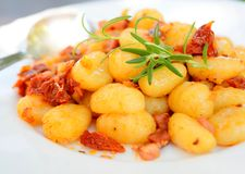 Gnocchi. With tomatoes, bacon and onion on the white plate Stock Photos