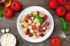 Gnocchi with tomatoes, mozzarella, mushrooms and basil, top view table scene over dark wood. Gnocchi with tomatoes, mozzarella, mushrooms and basil. Top view royalty free stock images