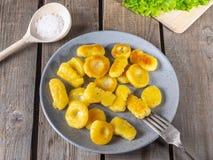 Gnocchina frit de pomme de terre d'un plat en céramique gris, feuilles de mensonge frais de laitue de feuille sur un panneau non  image libre de droits