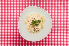 Gnocchiplaat op Rode en witte geruite lijst Stock Fotografie