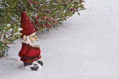 Gnom med rött hatt- och dräktanseende i snön Arkivfoton