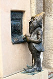 Gnome Banker. Close up of a metal bronze dwarf taking money from the ATM in the main square of Wroclaw, Poland royalty free stock image