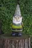 Gnome che sta sul ceppo di albero Immagine Stock Libera da Diritti