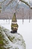 Gnome dalla parte che esamina il legno che sta sul ramo nevoso Fotografia Stock