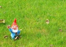 Gnome do jardim nas cores brilhantes que acenam na grama Fotografia de Stock Royalty Free