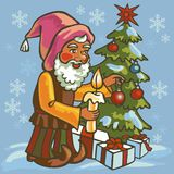 Gnome dress up Christmas tree. Gnome with a candle in his hand decorates the Christmas tree in winter Royalty Free Stock Photo