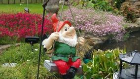 Gnome heureux sur une oscillation Photographie stock
