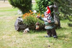 Gnome holding a lantern and smoking a pipe Stock Image