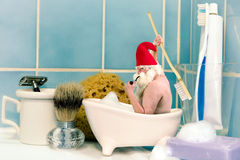 Gnome taking a bath. Funny old gnome taking a bath in a soap dish stock image