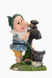Gnome with tap. Figurine of a gnome standing next to water tap and a bucket Royalty Free Stock Images
