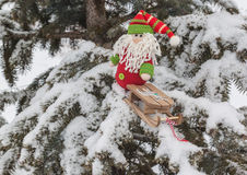 Gnome toy with sled on snow-covered tree branch mass produced p Royalty Free Stock Photos