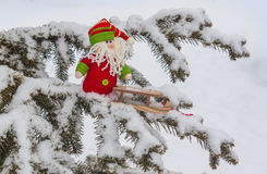Gnome toy with sled on snow-covered tree branch mass produced p Stock Photo