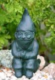 Gnome vert d'ornement de jardin s'asseyant sur des pierres Images stock