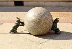 Gnomes Pushing Ball. Close up of two metal bronze dwarfs pushing a concrete ball in the main square of Wroclaw, Poland Royalty Free Stock Images