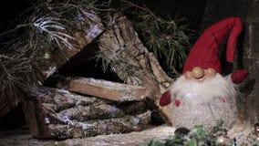 gnomo del Hada-cuento en un casquillo rojo de la Navidad en un fondo de una casa de madera con las luces del centelleo Composici? almacen de metraje de vídeo