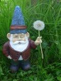 Gnomo del jardín con el sombrero y el diente de león azules Fotografía de archivo