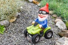 Gnomo del jardín que conduce una Patio-bici en un jardín Imagen de archivo libre de regalías