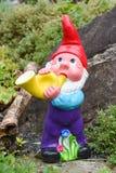 Gnomo del jardín que juega un cuerno en un jardín Foto de archivo libre de regalías