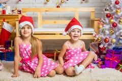 Gnomo divertido de la muchacha que se sienta en una estera en un ajuste de la Navidad Imagen de archivo libre de regalías