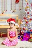 Gnomo divertido de la muchacha que se sienta en una estera en un ajuste de la Navidad Fotos de archivo libres de regalías