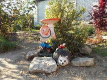Gnomo divertido en el jardín de flores en la cabaña Imagen de archivo