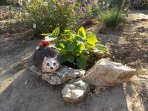 Gnomo divertido en el jardín de flores en la cabaña Imagenes de archivo