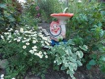 Gnomo divertido en el jardín de flores en la cabaña Fotos de archivo