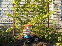 Gnomo divertido en el jardín de flores en la cabaña Fotografía de archivo libre de regalías