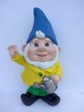 Gnomo do jardim com chapéu e o dente-de-leão azuis fotos de stock royalty free