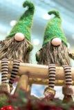 Gnomos do Natal em tampões verdes e em calças listradas Sente-se em um banco de madeira Natal feriado imagem de stock royalty free