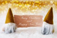 Gnomos nobles de oro con la tarjeta, Feliz Año Nuevo de la Feliz Navidad Foto de archivo