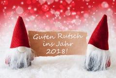 Gnomos rojos de Christmassy con Año Nuevo de los medios de Guter Rutsch 2018 Foto de archivo