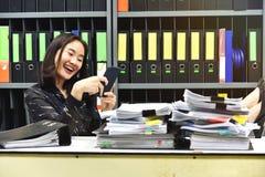 Gnuśna azjatykcia biurowa kobieta używa mobilnego mądrze telefon w pracującym czasie Zdjęcia Royalty Free