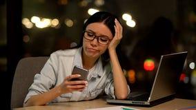 Gnu?na kobieta u?ywa telefon kom?rkowego przy miejsce pracy, unika nudn? prac?, zak??cenie spokoju zdjęcia stock