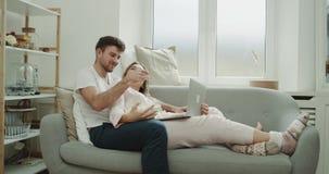 Gnuśny dzień dla młodego pary łasowania popkornu na kanapie i patrzeć przez notatnika jest ubranym piżamy zbiory