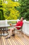 Gnuśny mężczyzna pije piwo na patiu podczas gdy outdoors Zdjęcie Stock